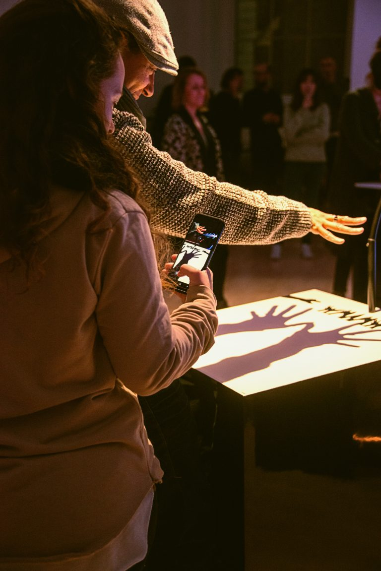 An adult and child participant create music together by casting shadows at Cave of Sounds, Music Hackspace, Somerset House Studios. Photo: Suzi Corker